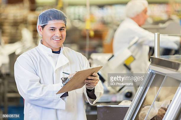 Supermarket employee working behind deli or butcher counter