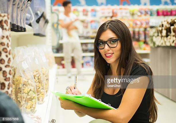 Supermercado Empregado de Balcão verificar produtos.  Cliente com cão no fundo