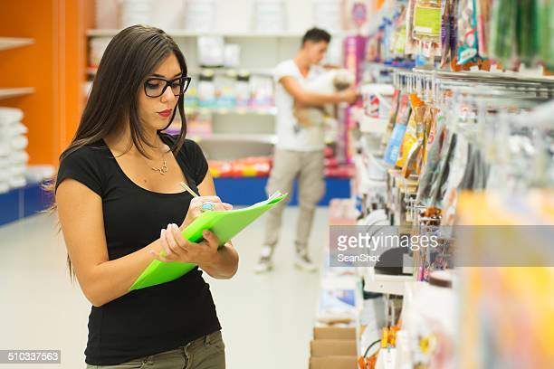 Supermarket Sales Clerk Checking Products. Customer with dog on Background