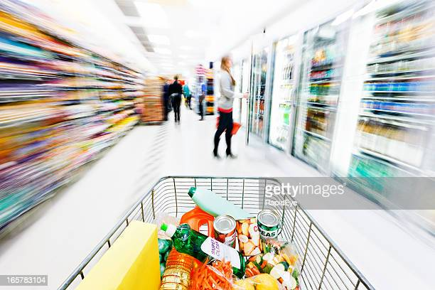 Supermarket shopping cart speeds down aisle, creating motion blur