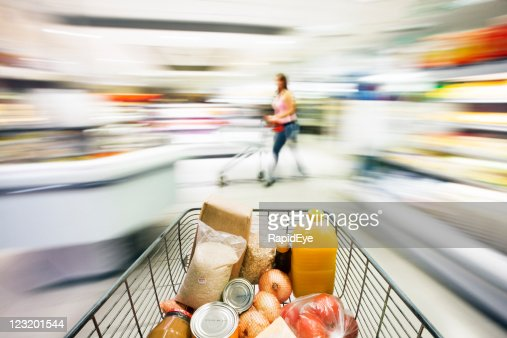 Supermarket trolley races through store with motion blur.