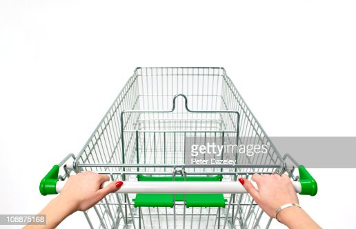 Supermarket trolley with woman's hands on white