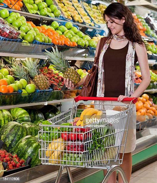 スーパーマーケット女性、パイナップルを選択