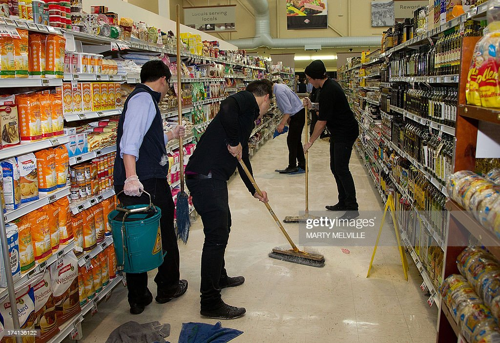 Supermarket workers clean up after a 6.5 magnitude earthquake hit Wellington on July 21, 2013. A strong earthquake struck off New Zealand, jolting the nation's capital but no tsunami alert was issued and there were no immediate reports of damage. AFP PHOTO / MARTY MELVILLE