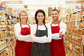 Supermarket Workers Standing In Grocery Aisle Smiling To Camera