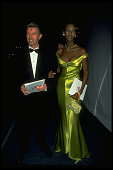 Supermodel Iman wearing shiny green gown by Versace while holding arm of rocker husband David Bowie at 7th on Sale AIDS benefit