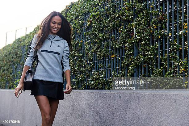 Supermodel Joan Smalls exits Bottega Veneta in a gray Puma pullover and short black skirt during the Milan Fashion Week Spring/Summer 16 on September...