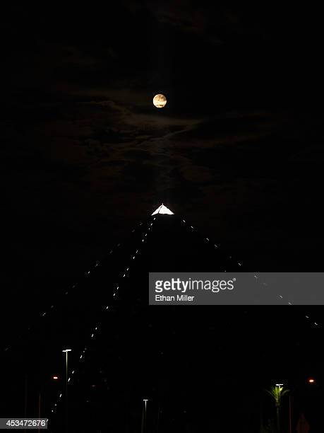 A supermoon rises behind the light on top of the Luxor Hotel and Casino on August 10 2014 in Las Vegas Nevada In the second supermoon or perigee moon...