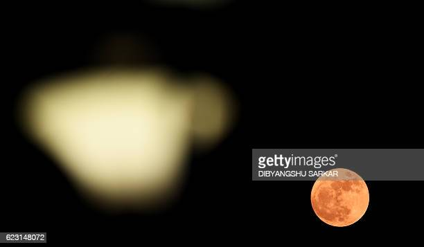 A 'supermoon rises in front of a street light in Kolkata on November 14 2016 Skygazers headed to highrise buildings ancient forts and beaches on...