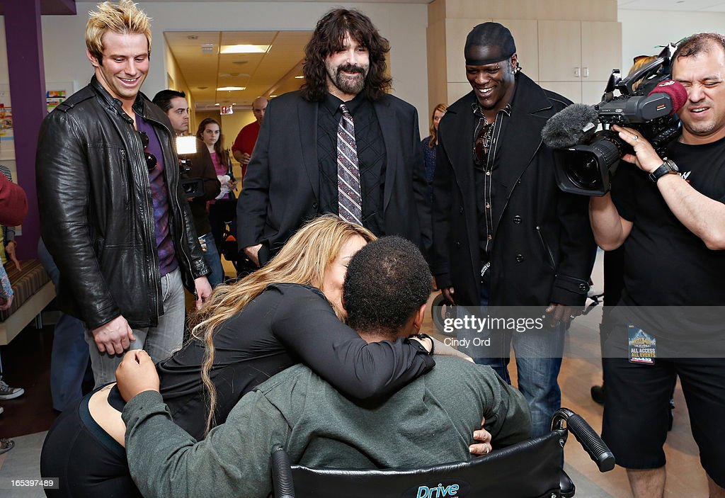WWE Superstar Zack Ryder, WWE Legend Mick Foley and WWE Superstar R-Truth look on as WWE Diva Layla El gives a paitent a kiss at St. Mary's Hospital For Children on April 3, 2013 in New York City.