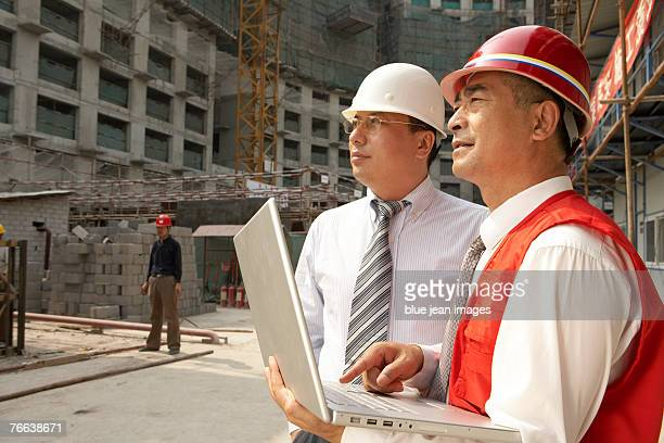 A supervisor and an investor use a computer on a construction site.