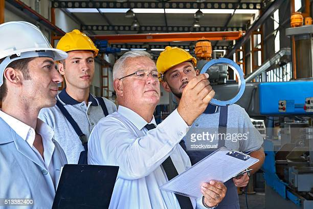 Supervisor and factory workers checking product