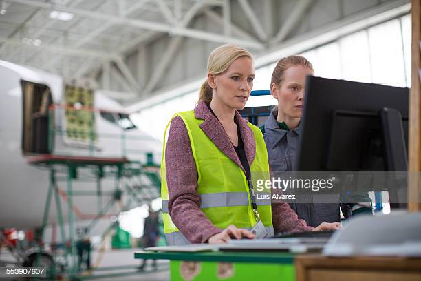 Supervisor and worker using computer in hangar