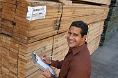 Supervisor Checking Inventory in Lumber Warehouse