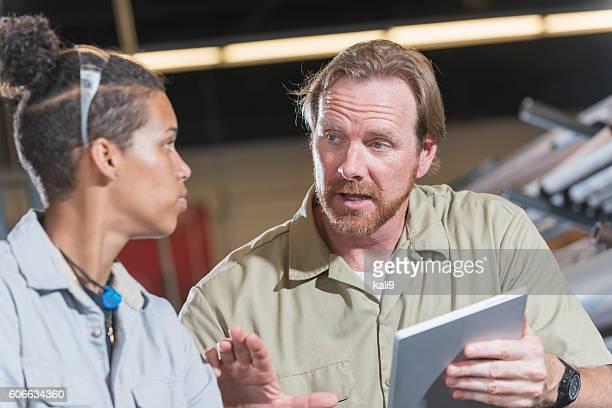 Supervisor, digital tablet, talking with female worker