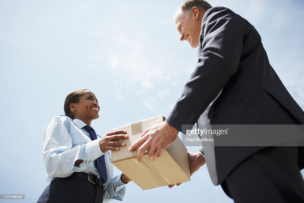 Supervisor handing box to worker : Stock Photo