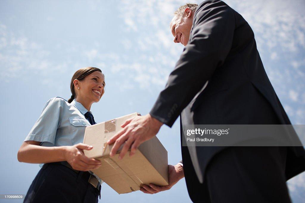 Supervisor handing box to worker : Stock Photo