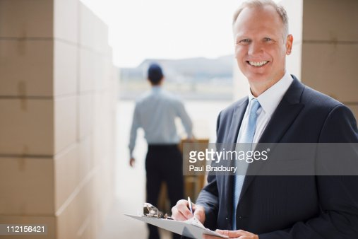 Supervisor holding clipboard in shipping area : Stock Photo