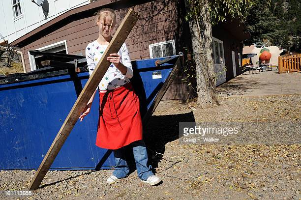 101309_BEARS_CFW Supervisor Kelly Bender uses a 2x4 to reenforce the cover of the dumpster at the Coney Island Hot Dog Restaurant in Bailey CO where...