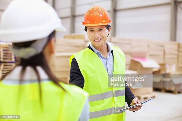 Supervisor shaking hands with trainee in distribution warehouse
