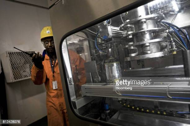 A supervisor stands on watch as a machine automatically seals diamonds sourced from the seabed in a barcoded tin can aboard the Mafuta diamond mining...