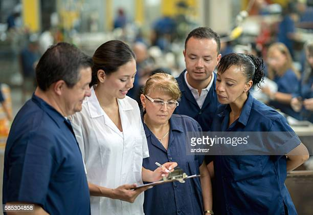 Supervisor talking to workers at a factory