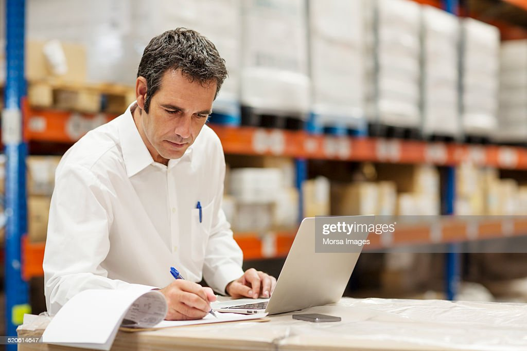 Supervisor working in warehouse : Stock Photo