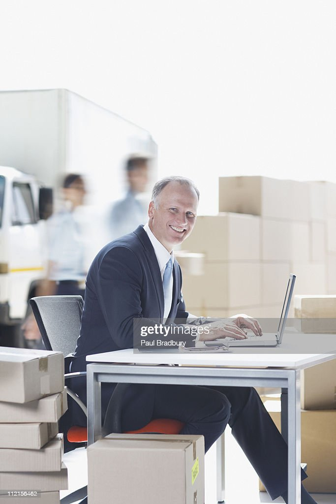 Supervisor working on laptop in shipping area : Stock Photo