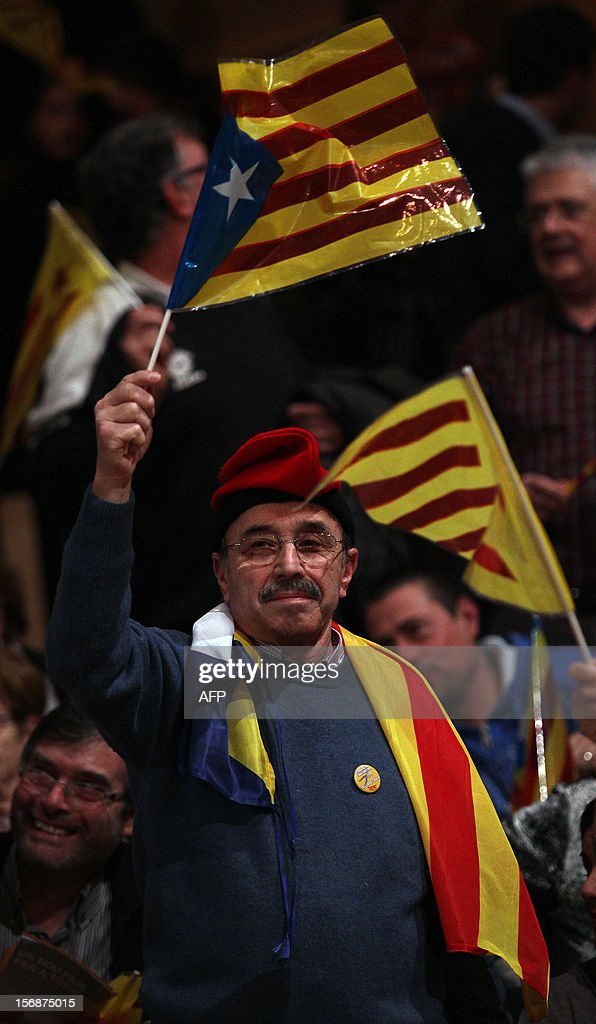 A supoorter of leader of Catalan party ERC (Esquerra Republicana de Catalunya - Republican Left from Catalonia) Oriol Junqueras waves an Estelada flag during a final campaign meeting on November 23, 2012 in Girona. Catalan will go to polling station on November 25 for regional elections. AFP PHOTO/ QUIQUE GARCIA