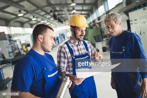 Supplier with engineer checking on production in factory : Stock Photo
