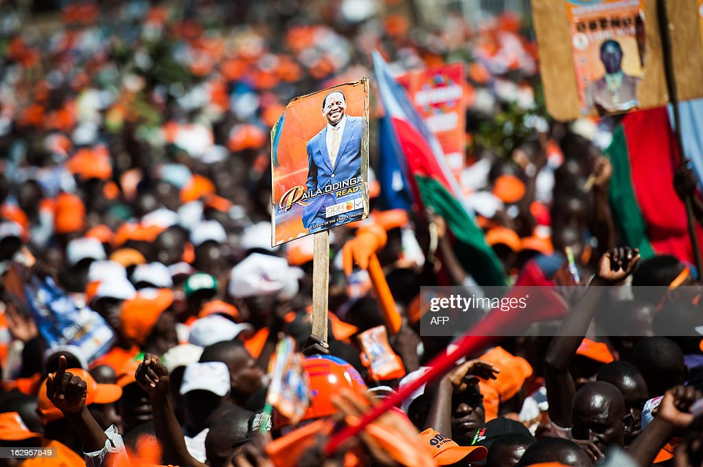 A supporet holds a poster of Kenyan Prime Minister and presidential candidate Raila Odinga during a rally for Odinga at Nairobi's Nyayo stadium, on March 2, 2013, on the last day of campaigning, 48 hours ahead of presidential, gubernatorial and senatorial elections. AFP PHOTO/PHIL MOORE