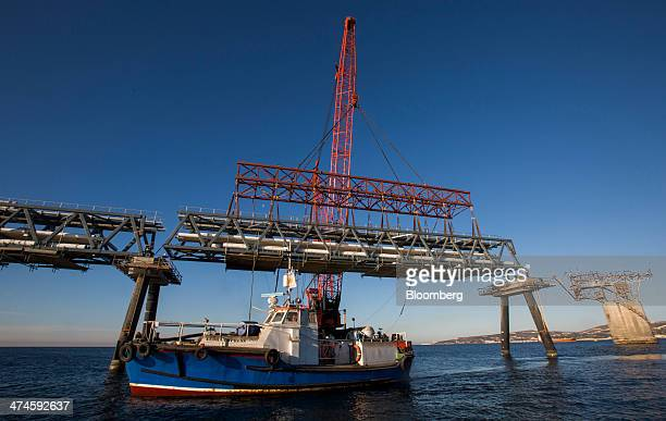 A support boat floats on the Mediterranean Sea beside jetty support legs as a section of fuel pipe is lowered into position at the VTTV oil storage...