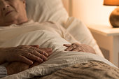 Close-up of hand of senior on hand of dying elderly person as sign of support during sickness