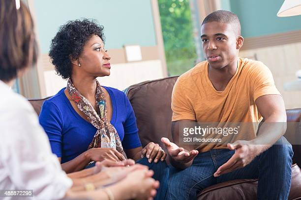Support group listening to young man telling story during meeting