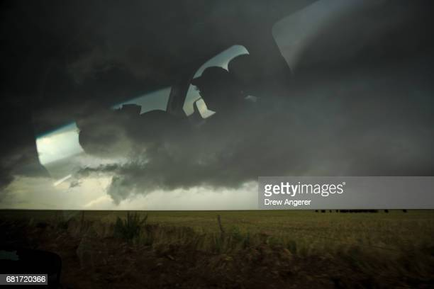 Support scientist Rachel Humphrey is reflected in the window of a tornado scout vehicle as she drives toward a supercell thunderstorm May 10 2017 in...