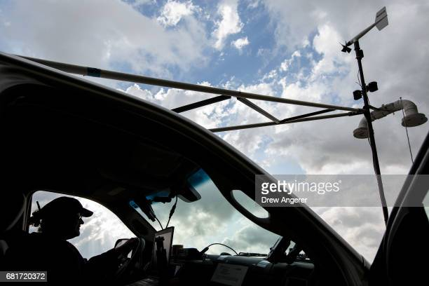 Support scientist Rachel Humphrey relaxes in the tornado scout vehicle at the end of a day of chasing supercell thunderstorms in hopes of...