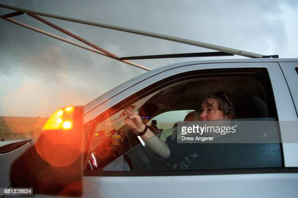 Support scientist Rachel Humphrey stays in the driver's seat of the tornado scout vehicle as she observes a supercell thunderstorm as it bears down...