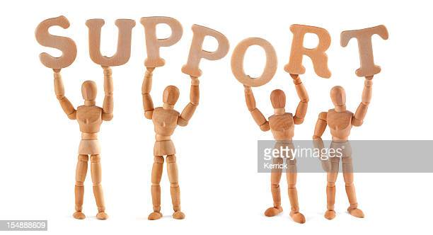 Support - wooden mannequin holding this word