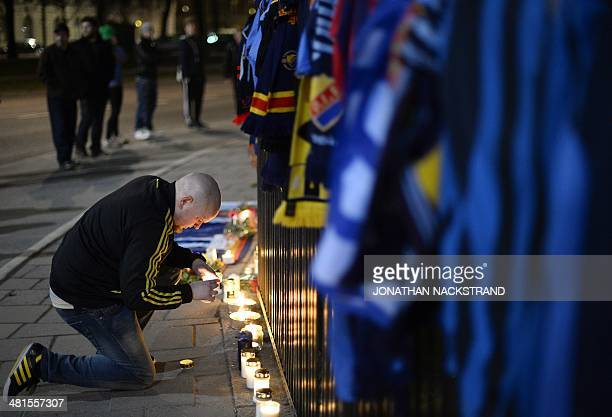 A supporter AIK football club pays his respects outside Stockholms Stadion laying down flowers and jerseys after a Djurgarden IF supporter got...