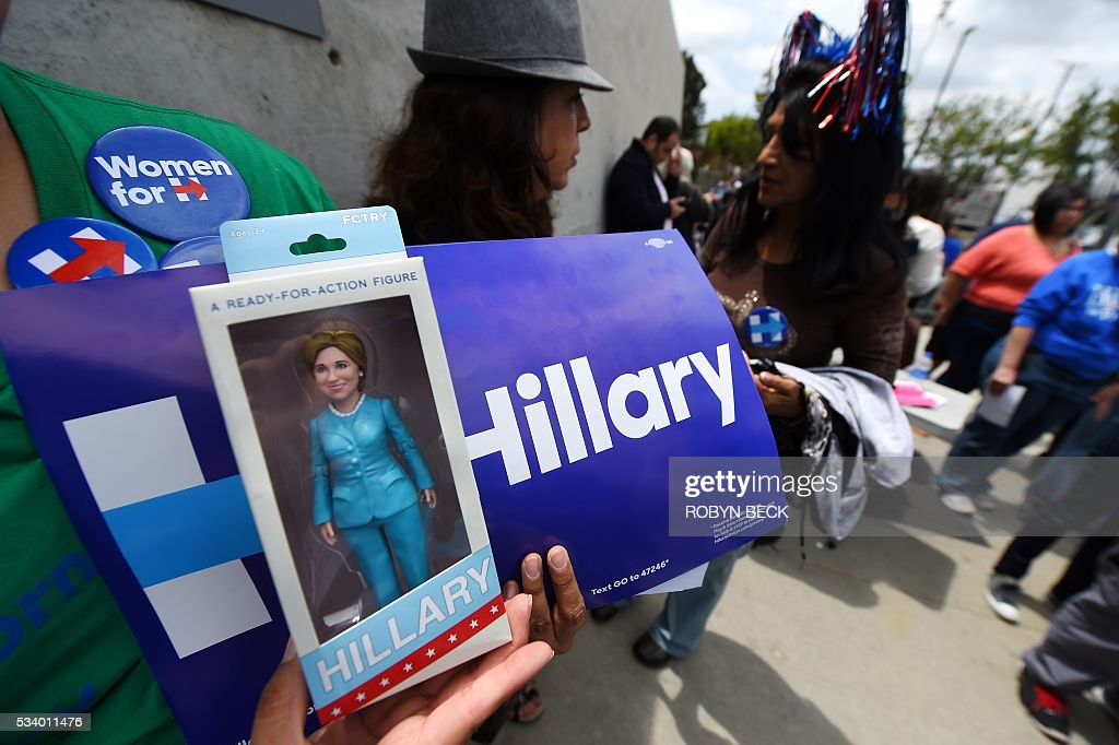 Supporter Angie Melendez holds a Hillary Clinton action figure as she waits in line to hear the Democratic presidential hopeful speak, May 24, 2016, at a campaign event in the city of Commerce, outside of Los Angeles, California, May 24, 2016. / AFP / Robyn BECK