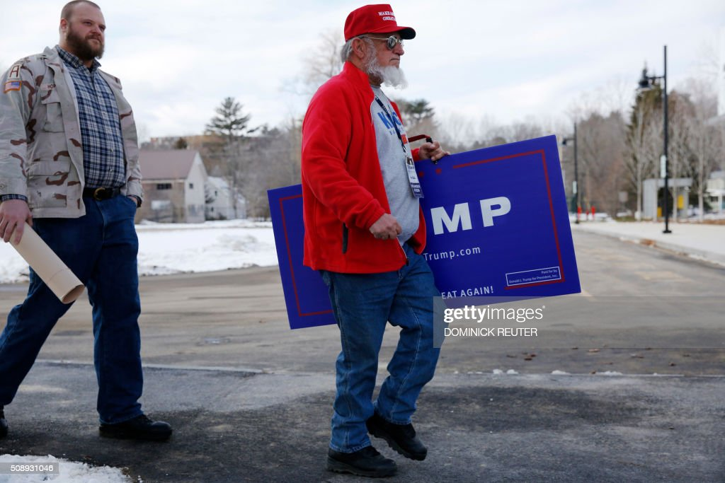 A supporter carries a sign before a rally for Republican presidential candidate Donald Trump at Plymouth State University, February 7, 2016, in Plymouth, New Hampshire. / AFP / DOMINICK REUTER