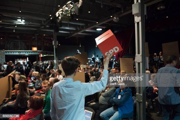 A supporter collects sheets in box with a SPD logo during a welcome meeting for new SPD members in Berlin on March 22 2017 in Berlin Germany Since...