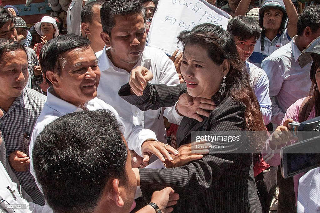 A supporter cries while trying to hug opposition Cambodian National Rescue Party leader <a gi-track='captionPersonalityLinkClicked' href=/galleries/search?phrase=Kem+Sokha&family=editorial&specificpeople=659005 ng-click='$event.stopPropagation()'>Kem Sokha</a> during a gathering near the barricades set up to impede access to demonstrators, human rights observers and members of the press to the Municipal Court on July 16, 2014 in Phnom Penh, Cambodia. Hundreds of protesters demonstrate outside of the Phnom Penh Municipal Court of First Instance in support of five elected Members of Parliament from the opposition Cambodian National Rescue Party in Phnom Penh, Cambodia. Yesterday, 15 July 2014, parliamentarians Mu Sochua, Ho Vann, Men Sothavrin and Keo Phirum were arrested after demonstrations Tuesday morning turned violent, with several municipal security guards severely beaten by protesters. Two other CNRP members were arrested on Wednesday: Real Khemarin and Ouer Narith. The parliamentarians were held overnight by the authorities and brought to court early today morning for questioning by the investigative judge.