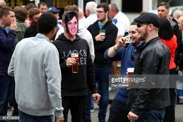 QPR supporter enjoys a drink with friends outside the stadium wearing a Stan Bowles face mask ahead of the former player's benefit match and the...