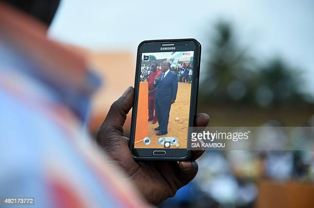 A supporter films with a smartphone Former Ivoirian Prime Minister and candidate for the upcoming presidential election Charles Konan Banny speaking...