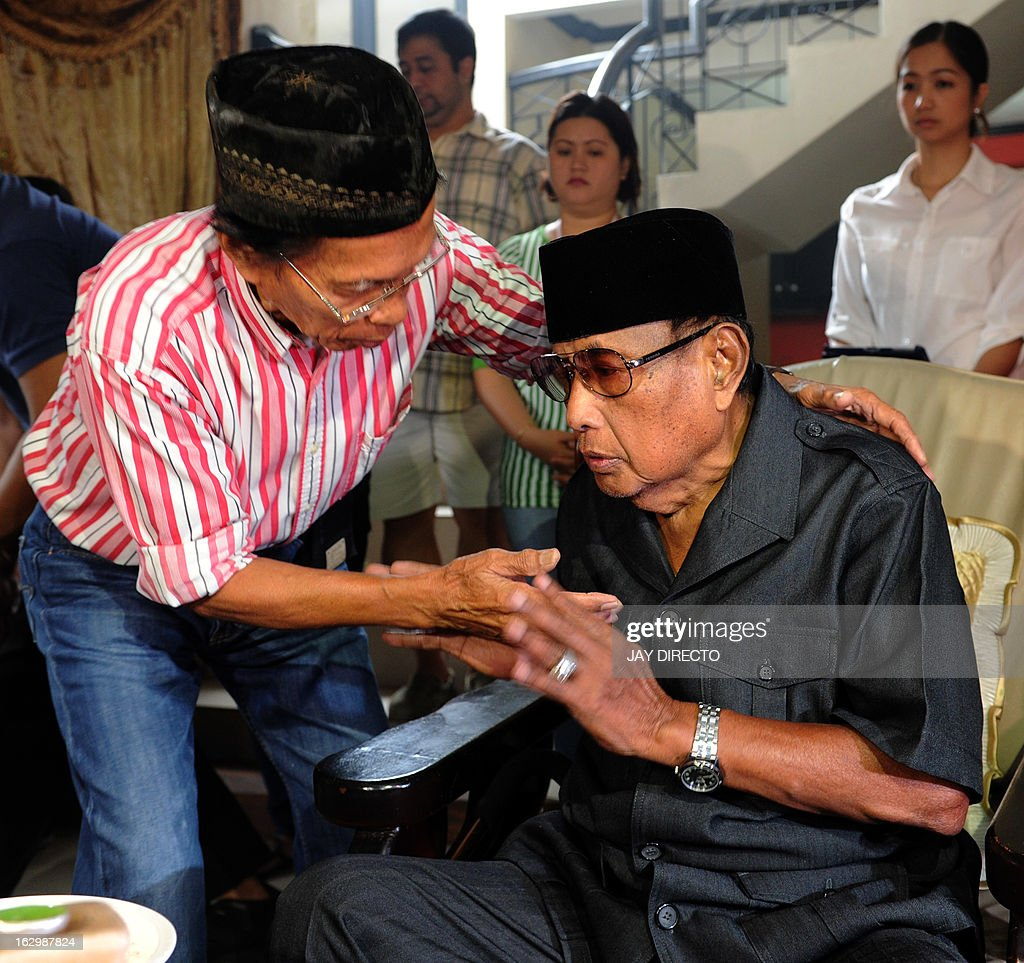 A supporter greets the self-proclaimed leader of the Sultanate of Sulu Jamalul Kiram III (R) at his home in Manila on March 3, 2013. Meanwhile, five Malaysian policemen died in a fresh clash with gunmen as violence linked to a deadly stand-off with Filipino intruders spread to another area of Borneo island, police said on March 3. AFP PHOTO / Jay DIRECTO