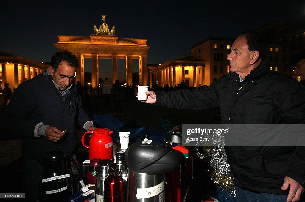 A supporter (R) helps Sadegh Farahani, a refugee from Iran, to prepare a cup of tea on the seventh day of a hunger strike in front of the Brandenburg Gate on October 31, 2012 in Berlin, Germany. Sadegh and other demonstrators, predominantly from Iran, Afghanistan and Iraq, are subsisting on only water, tea and coffee without sugar. Despite the cold temperatures they have been forbidden by the police from having blankets, tents, or isomattresses, as the possession of which would change the official status of the protest, registered in advance, from a 'demonstration' to a 'camp'. They have been sitting in front of the Brandenburg Gate since October 24 and say they will continue their strike until the German government responds to their demands for a halt to deportations and faster processing of asylum applications. Meanwhile the police have been criticized by local party-affiliated as well as non-partisan activist groups for their restrictions.