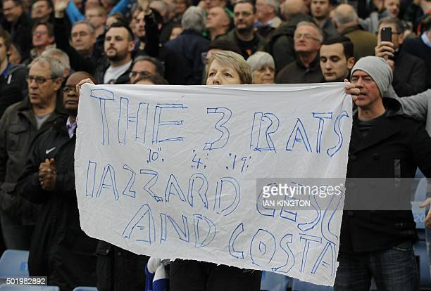A supporter holds a banner against certain Chelsea players before the English Premier League football match between Chelsea and Sunderland at...