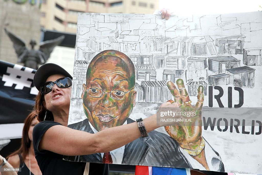 A #ZUMAMUSTFALL supporter holds a banner picturing South African president Jacob Zuma as she demonstrates against him on February 11, 2016 in Durban, few hours ahead of his annual State of the Nation Address (SONA)at the South African Parliament in Cape Town. Factors fuelling the calls for Zuma to quit include public money spent on his private residence, damage done to the economy when he fired two finance ministers within days, and government corruption. His address to parliament comes just two days after the Constitutional Court heard a crucial case accusing the president of violating his oath to uphold the constitution. JANTILAL