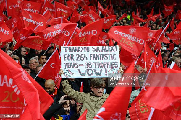 A supporter holds a banner showing support for Manchester United's Scottish manager Alex Ferguson in a sea of red flags during the English Premier...